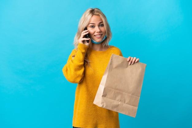 Młoda rosjanka trzyma torbę na zakupy spożywcze na białym tle na niebieskim tle prowadzenie rozmowy z telefonem komórkowym z kimś