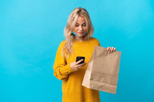Młoda rosjanka trzyma torbę na zakupy spożywcze na białym tle na niebieskim tle, wysyłając wiadomość z telefonu komórkowego