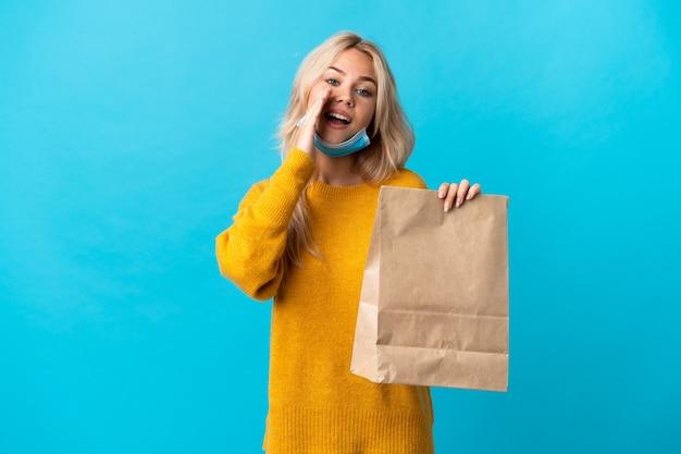 Młoda rosjanka trzyma torbę na zakupy spożywcze na białym tle na niebiesko krzycząc z szeroko otwartymi ustami