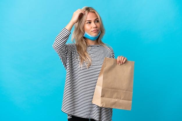 Młoda rosjanka trzyma torbę na zakupy spożywcze na białym tle na niebiesko, mając wątpliwości podczas drapania głowy