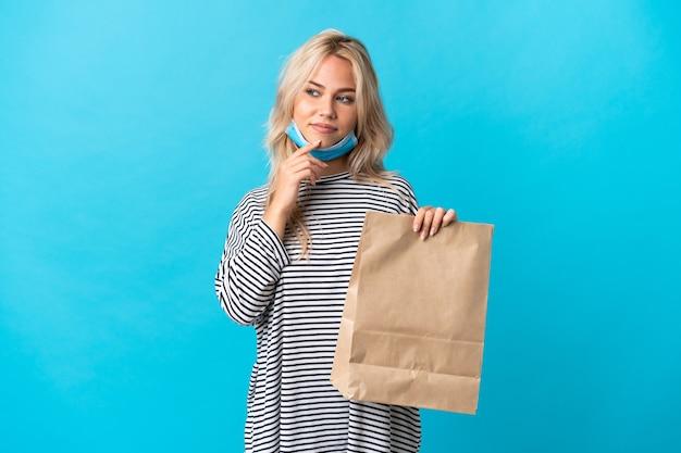 Młoda rosjanka trzyma torbę na zakupy spożywcze na białym tle na niebiesko, patrząc z boku i uśmiechnięta
