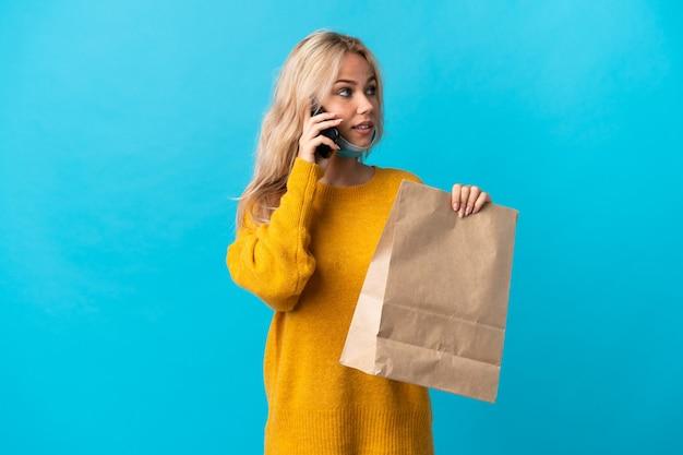 Młoda rosjanka trzyma torbę na zakupy spożywcze na białym tle na niebiesko prowadzenie rozmowy z telefonem komórkowym z kimś