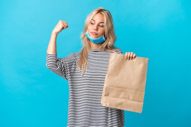Młoda rosjanka trzyma torbę na zakupy spożywcze na białym tle na niebiesko, robi silny gest