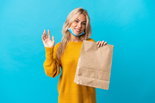 Młoda rosjanka trzyma torbę na zakupy spożywcze na białym tle na niebiesko salutowanie ręką z happy wypowiedzi