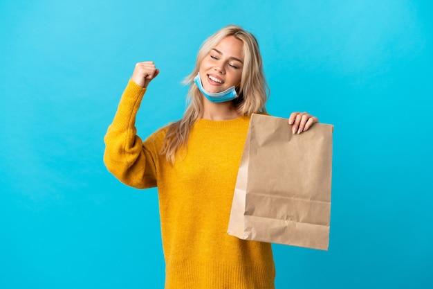 Młoda rosjanka trzyma torbę na zakupy spożywcze na białym tle na niebiesko świętuje zwycięstwo