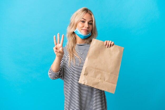 Młoda rosjanka trzyma torbę na zakupy spożywcze na białym tle na niebiesko szczęśliwa i liczy trzy palcami