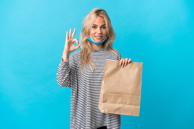 Młoda rosjanka trzyma torbę na zakupy spożywcze na białym tle na niebiesko wyświetlono znak ok palcami