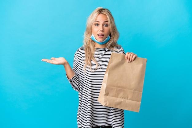 Młoda rosjanka trzyma torbę na zakupy spożywcze na białym tle na niebiesko z zszokowany wyraz twarzy