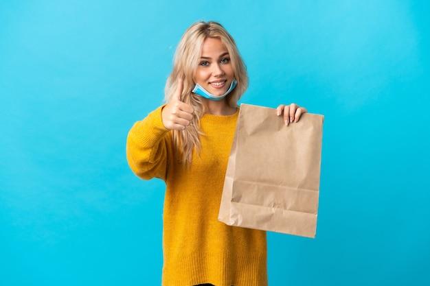 Młoda rosjanka trzyma torbę na zakupy spożywcze na niebieskim tle z kciukami do góry, ponieważ stało się coś dobrego