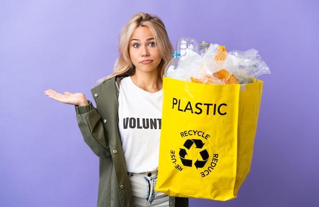 Młoda rosjanka trzyma worek recyklingu pełen papieru do recyklingu na białym tle na fioletowej ścianie, mając wątpliwości podczas podnoszenia rąk