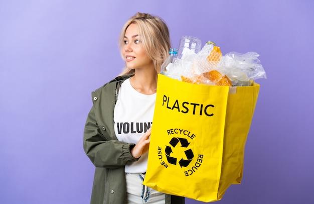 Młoda rosjanka trzyma worek recyklingu pełen papieru do recyklingu na białym tle na fioletowej ścianie, patrząc z boku i uśmiechnięty