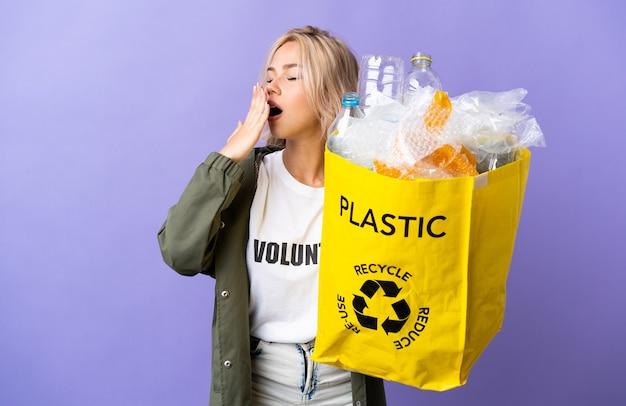 Młoda rosjanka trzyma worek recyklingu pełen papieru do recyklingu na białym tle na fioletowej ścianie ziewanie i obejmowanie ręką szeroko otwarte usta