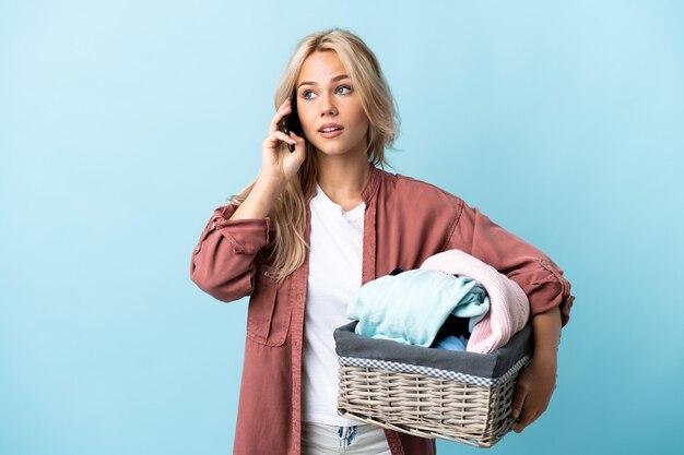 Młoda rosjanka trzymając kosz na ubrania na białym tle na niebiesko prowadzenie rozmowy z telefonem komórkowym