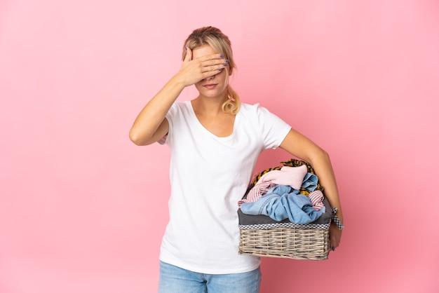 Młoda rosjanka trzymając kosz na ubrania na białym tle na różowym tle zasłaniające oczy rękami. nie chcę czegoś widzieć