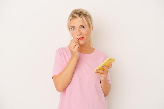 Młoda rosjanka trzymając telefon komórkowy na białym tle z palcami na ustach zachowując tajemnicę.