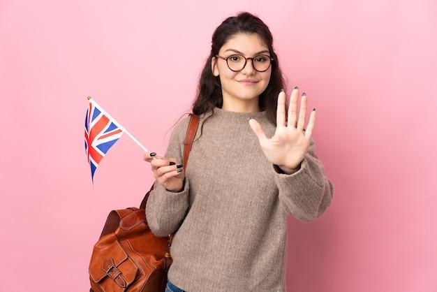 Młoda rosjanka trzymająca flagę wielkiej brytanii na białym tle na różowym tle, licząc pięć palcami