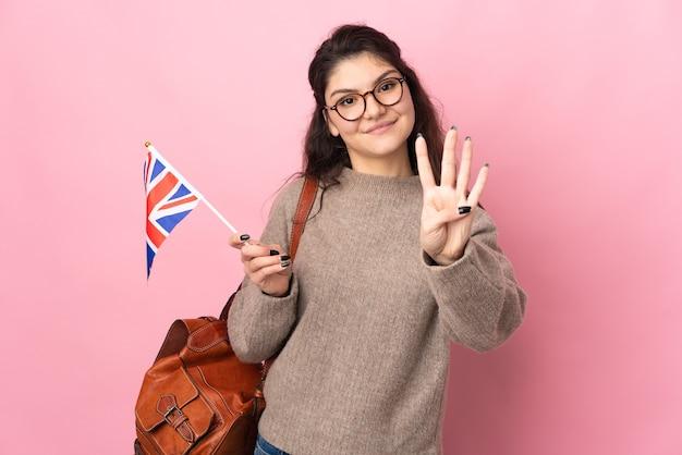 Młoda rosjanka trzymająca flagę wielkiej brytanii na białym tle na różowym tle szczęśliwa i licząca cztery palcami