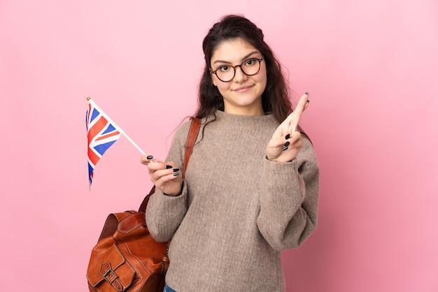 Młoda rosjanka trzymająca flagę wielkiej brytanii na białym tle na różowym tle z palcami skrzyżowanymi i życzącymi wszystkiego najlepszego