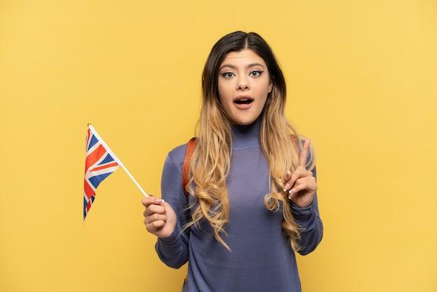Młoda rosjanka trzymająca flagę wielkiej brytanii na żółtym tle, myśląca o pomyśle wskazującym palec w górę finger