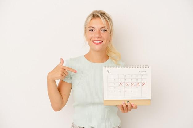 Młoda rosjanka trzymająca kalendarz na białym tle osoba wskazująca ręką miejsce na koszulce, dumna i pewna siebie
