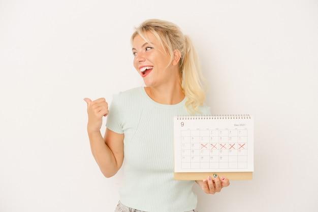 Młoda rosjanka trzymająca kalendarz na białym tle wskazuje palcem kciuka, śmiejąc się i beztrosko.