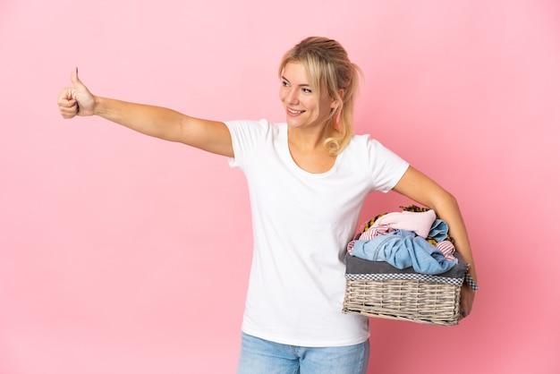 Młoda rosjanka trzymająca kosz na ubrania na białym tle na różowym tle dająca kciuk w górę gestu