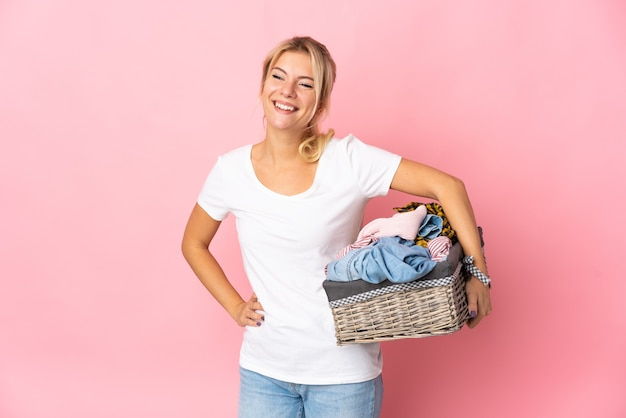 Młoda rosjanka trzymająca kosz na ubrania na białym tle na różowym tle pozuje z rękami na biodrach i uśmiecha się