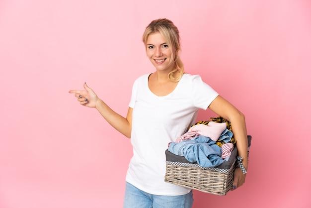 Młoda rosjanka trzymająca kosz na ubrania na białym tle na różowym tle wskazujący palec w bok