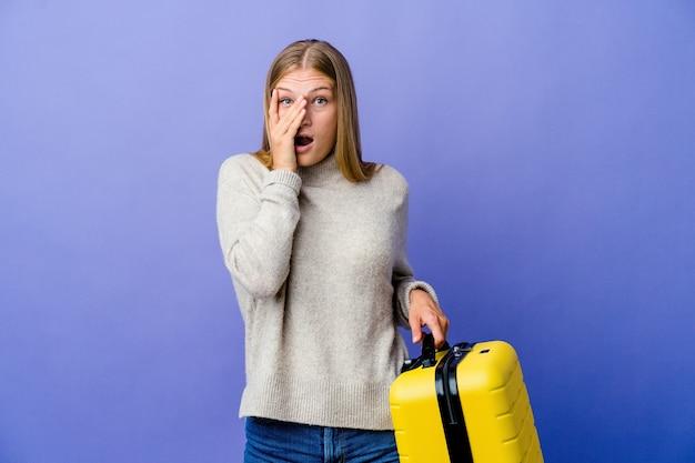 Młoda rosjanka trzymająca walizkę w podróży mruga przez palce przestraszona i zdenerwowana.