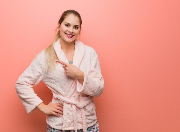 Młoda rosjanka ubrana w piżamę, uśmiechając się i wskazując w bok