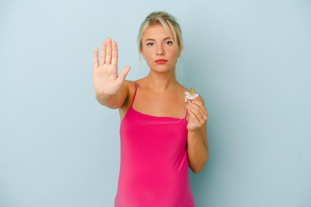 Młoda rosjanka w ciąży trzyma smoczek na białym tle na niebieskim tle stojąc z wyciągniętą ręką pokazując znak stop, uniemożliwiając.
