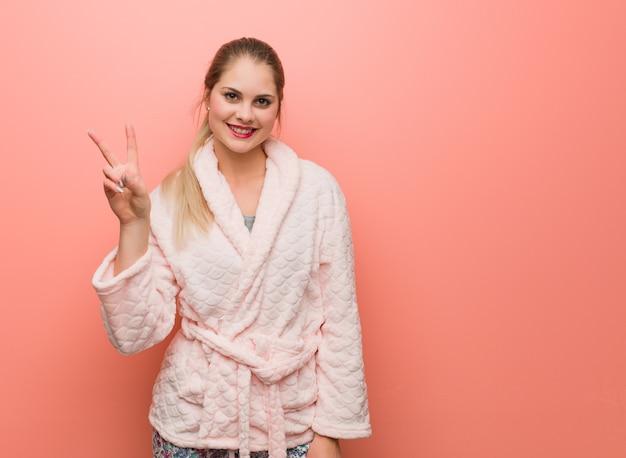 Młoda rosjanka w piżamie pokazuje numer dwa