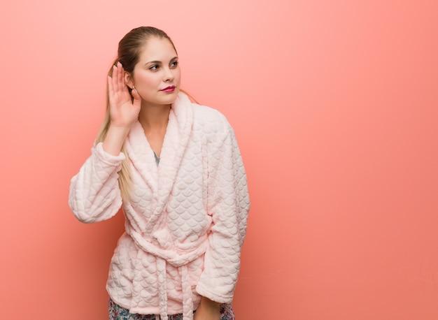 Młoda rosjanka w piżamie próbuje słuchać plotek