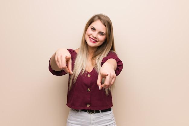 Młoda rosjanka, wesoła i uśmiechnięta, wskazując na przód
