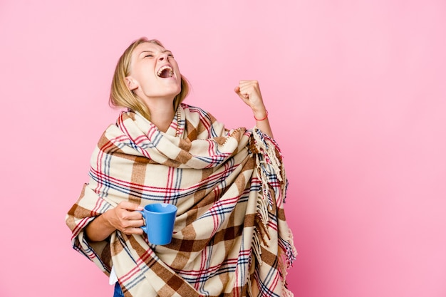 Młoda rosjanka zawinięta w koc picia kawy podnosząc pięść po zwycięstwie, koncepcja zwycięzcy.