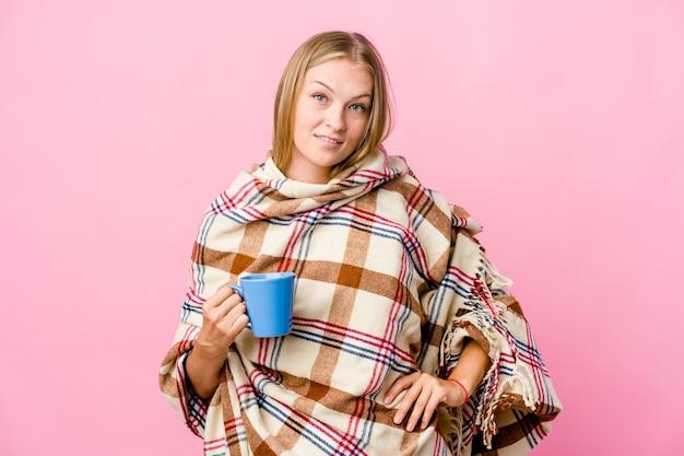 Młoda rosjanka zawinięta w koc pije kawę pewnie trzymając ręce na biodrach.