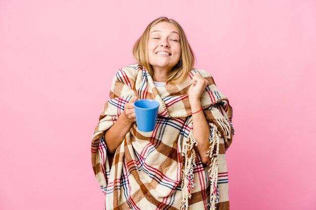 Młoda rosjanka zawinięta w koc pije kawę podnosząc pięść, czując się szczęśliwa i odnosząca sukcesy. koncepcja zwycięstwa.