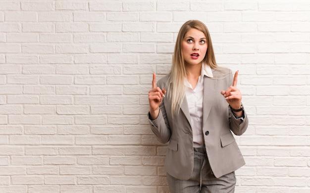 Młoda rosyjska biznesowa kobieta zdziwiona, wskazując w górę, aby coś pokazać