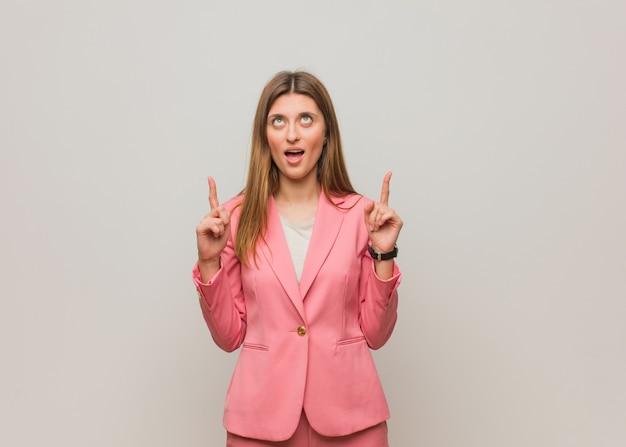 Młoda rosyjska dziewczyna biznesu zdziwiona, wskazując w górę, aby coś pokazać