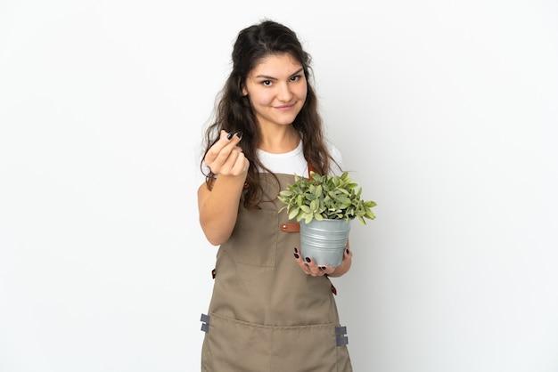 Młoda rosyjska dziewczyna ogrodnik trzyma roślinę na białym tle zarabianie pieniędzy gest
