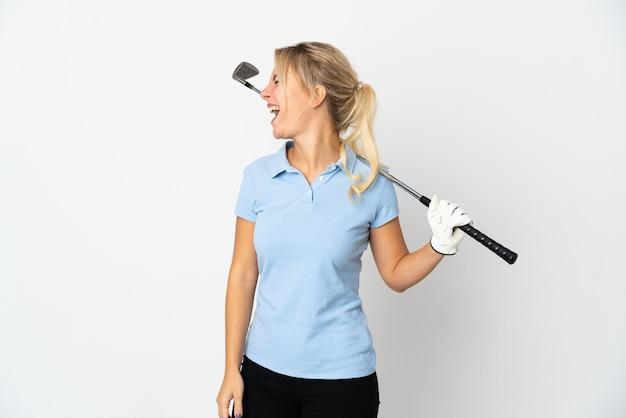 Młoda rosyjska golfistka na białym tle śmiejąca się w pozycji bocznej