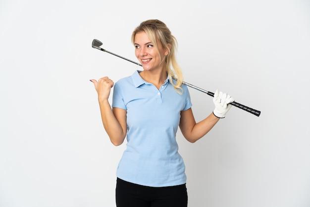 Młoda rosyjska golfistka na białym tle wskazująca na bok, aby zaprezentować produkt