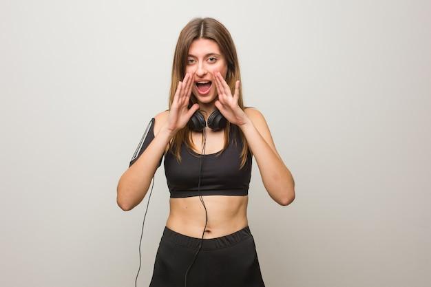 Młoda Rosyjska Kobieta Fitness Krzyczy Coś Szczęśliwego Do Przodu Premium Zdjęcia