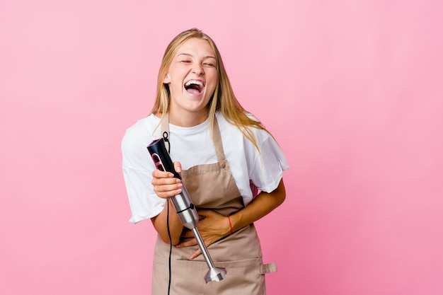 Młoda rosyjska kucharka trzymająca mikser elektryczny na białym tle śmieje się radośnie i dobrze się bawi trzymając ręce na brzuchu.