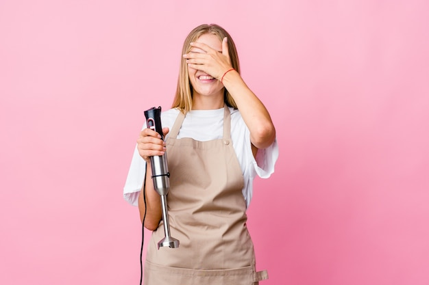 Młoda rosyjska kucharka trzymająca mikser elektryczny na białym tle zakrywa oczy rękami, uśmiecha się szeroko, czekając na niespodziankę.