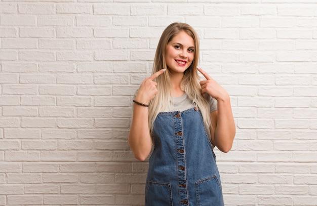 Młoda rosyjska modniś kobieta ono uśmiecha się, wskazuje usta