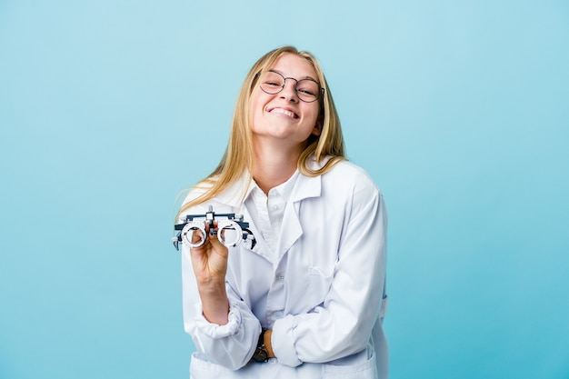 Młoda rosyjska optometrysta kobieta na niebiesko, śmiejąc się i zabawy.