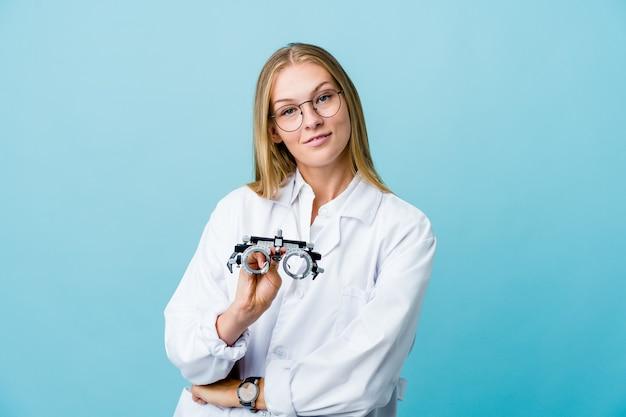 Młoda rosyjska optometrystka na niebiesko, która czuje się pewnie, z determinacją krzyżuje ręce.