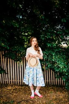 Młoda rosyjska piękność. atrakcyjna dziewczyna w długiej spódnicy w stylu retro, białym topie w starym stylu i kręconych rudych włosach i słomkowym kapeluszu pozuje do aparatu z płotem i zielonymi drzewami