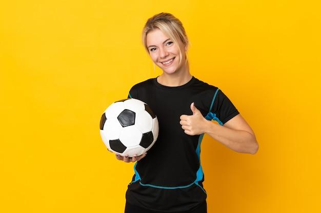 Młoda rosyjska piłkarka odizolowana na żółtym tle dająca gest kciuka w górę